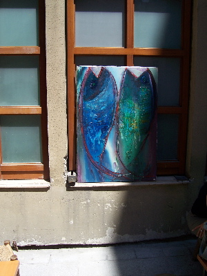 two fish.jpg A painting of two colorful fish, displayed in a window at an angle with the sun leaving one partly in shadow