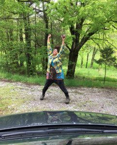Colorfully dressed black woman jumping in the air, surrounded by trees at a driveway.