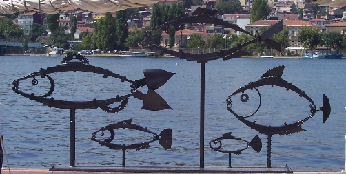 metal sculpture, outline of 5 fish, framed against the Bosphorus sea and Istanbul shoreline